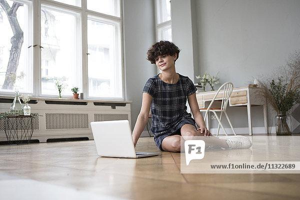 Junge Frau sitzt zu Hause auf dem Boden und schaut auf den Laptop.