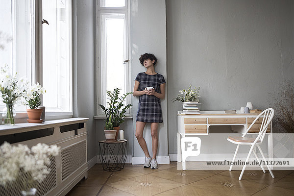 Junge Frau mit Kaffeetasse beim Blick durchs Fenster zu Hause