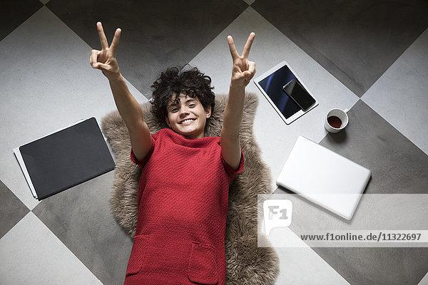 Porträt einer glücklichen jungen Frau  die zu Hause auf dem Boden liegt und Siegeszeichen zeigt.