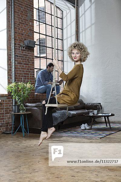Junge Frau sitzt auf Schaukel im Wohnzimmer  Mann liest im Hintergrund