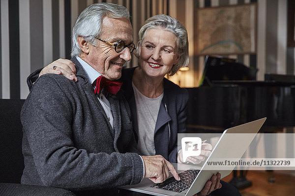 Glückliche Seniorenpaare beim Online-Shopping zu Hause
