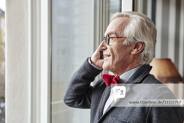 Smiling senior man on the phone at the window