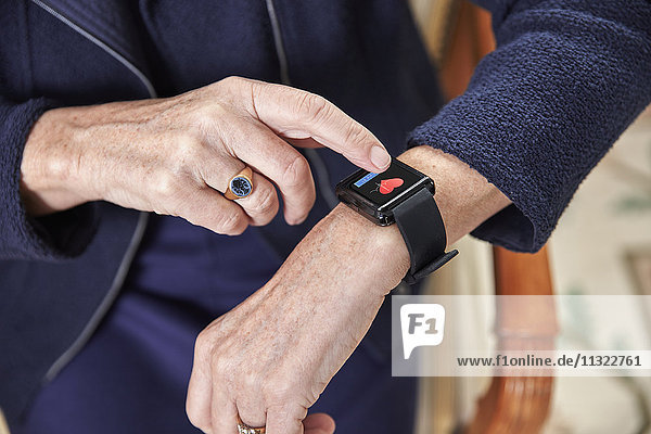 Seniorin überprüft medizinische Daten auf smartwatch