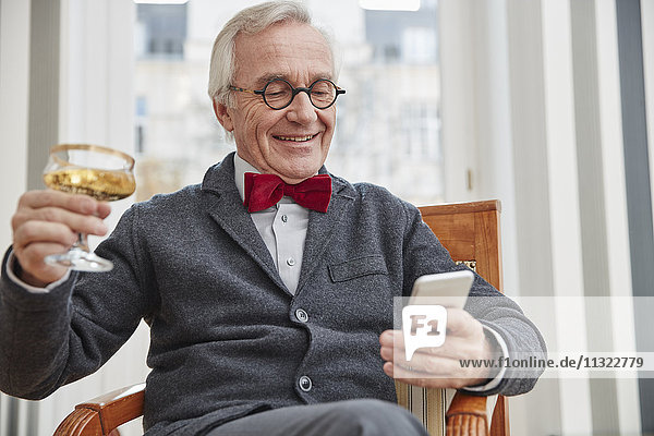 Smiling senior man with cell phone sitting on chair holding champagne glass