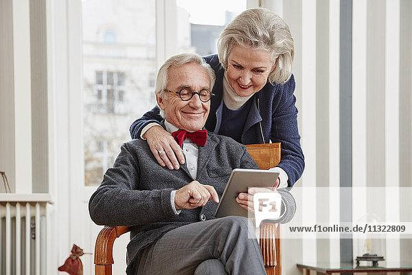 Lächelndes Seniorenpaar mit Tablette