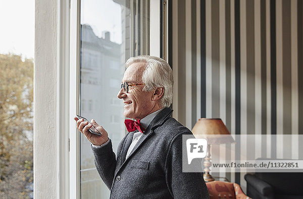 Senior man using cell phone at the window
