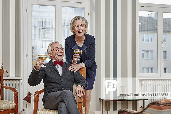 Glückliches Seniorenpaar trinkt Champagner zu Hause