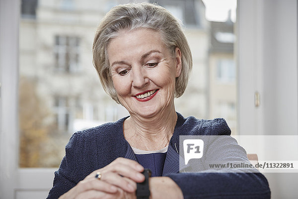 Lächelnde Seniorin schaut auf die Uhr