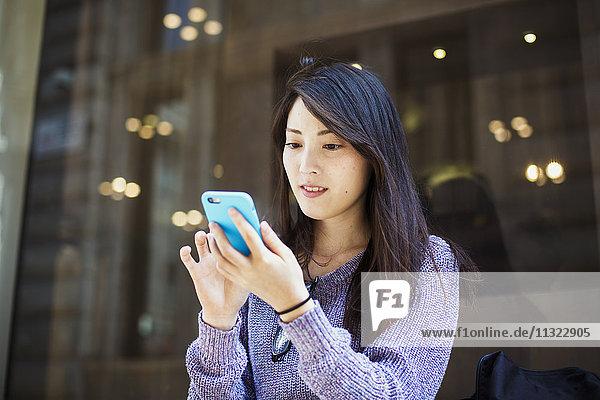 Junge Japanerin genießt einen Tag in London und benutzt ein Smartphone.