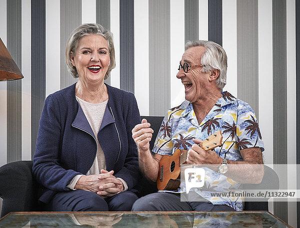 Glückliches Seniorenpaar mit Mann in hawaiianischem Hemd beim Ukulelele spielen