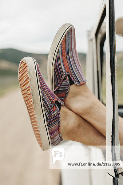 Feet of a man sticking out of a jeep window