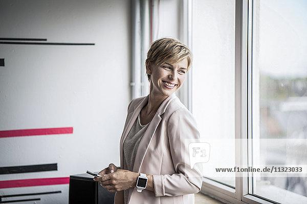 Lächelnde Geschäftsfrau am Fenster