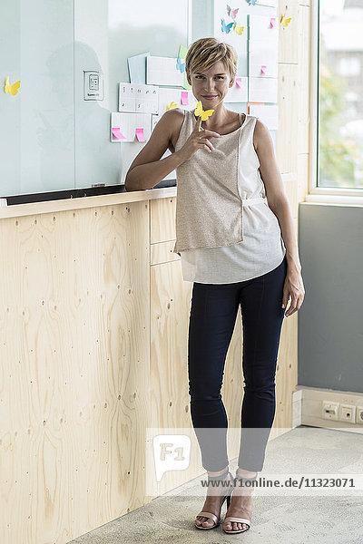 Geschäftsfrau mit Haftnotizen am Whiteboard im modernen Büro