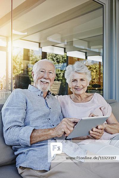 Seniorenpaar auf der Terrasse sitzend mit digitalem Tablett