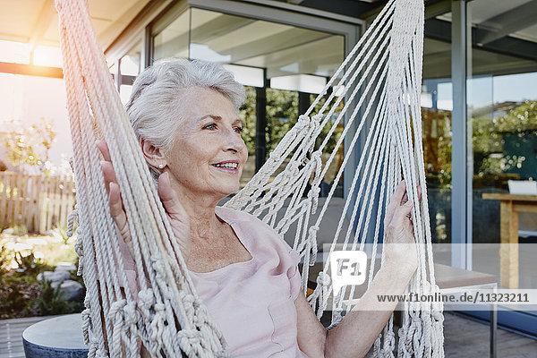 Seniorin sitzend in der Hängematte auf der Terrasse
