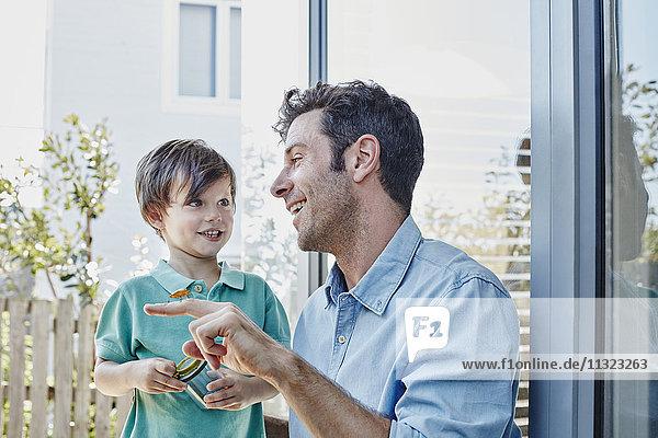 Vater und Sohn fangen zusammen eine Grille.