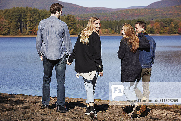 Four people walking along  couples hand in hand  on the shore of a lake.