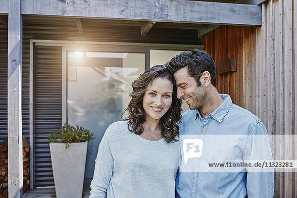 Paar steht vor der Tür ihres Hauses