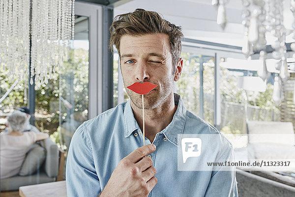 Mann mit Papierlippen vor dem Mund