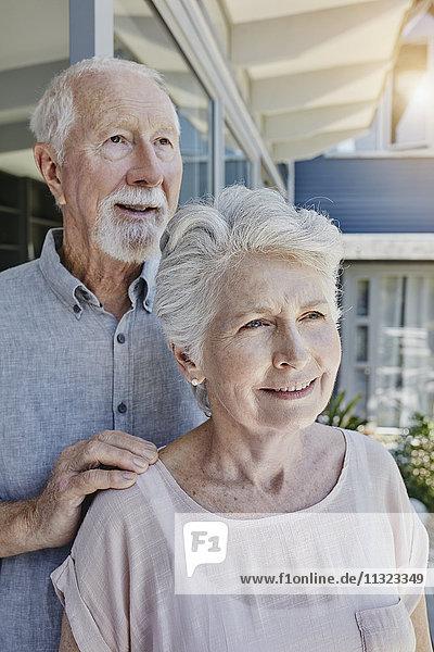 Senoir Paar steht in ihrem Haus und sieht zuversichtlich aus.
