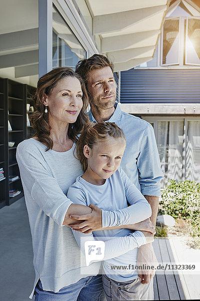 Glückliche Familie  die auf der Terrasse steht und die Tochter umarmt.
