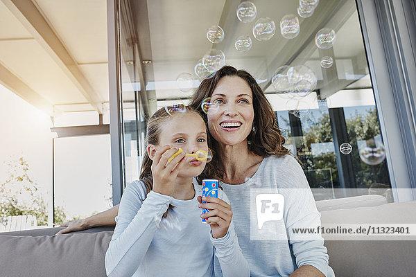 Mutter und Tochter blasen Seifenblasen auf der Terrasse