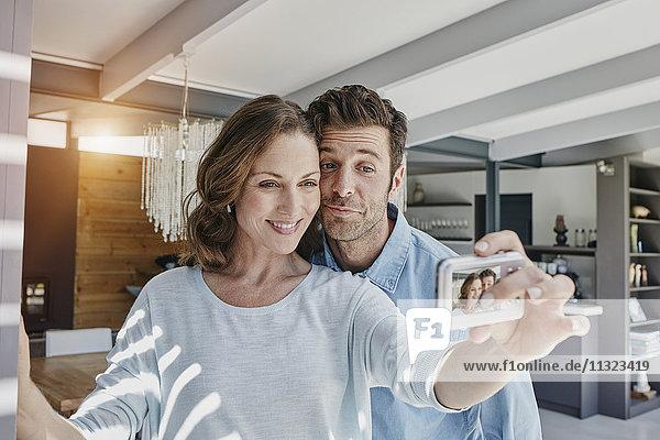 Glückliches Paar fotografiert sich zu Hause