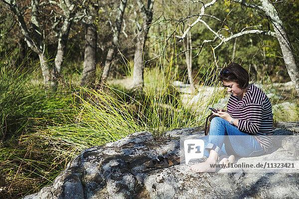 Eine Frau sitzt auf den Felsen im Schatten eines Flusses und schaut auf ein Smartphone.