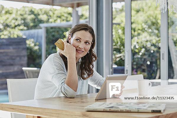 Frau sitzt auf der Terrasse und bezahlt online mit Kreditkarte.