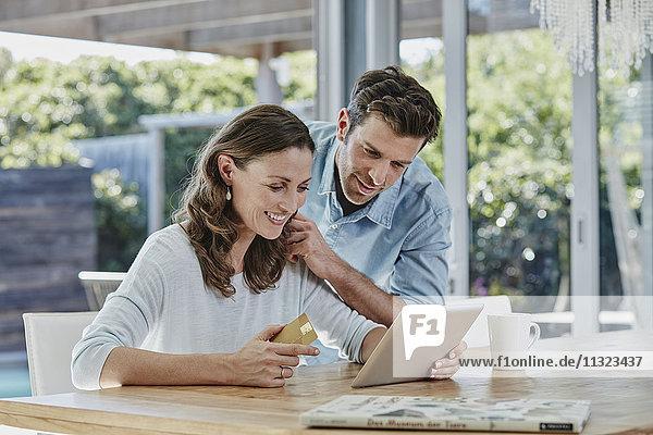 Seniorenpaar bei der Online-Zahlung mit Kreditkarte