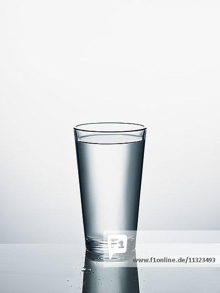 Wasserglas vor weißem Hintergrund