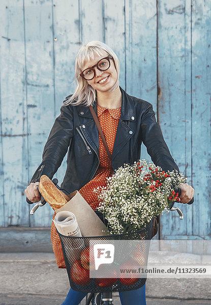 Lächelnde junge Frau mit Lebensmitteln auf dem Fahrrad Lächelnde junge Frau mit Lebensmitteln auf dem Fahrrad