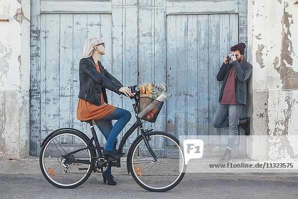 Junger Mann beim Fotografieren seiner Freundin auf dem Fahrrad