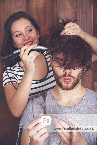 Junger Mann bekommt einen Haarschnitt von seiner Freundin mit einer Haarschneidemaschine.