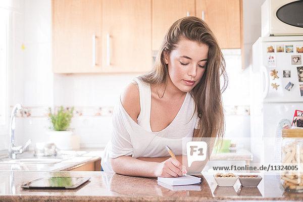 Junge Frau schreibt auf Notizblock in der Küche