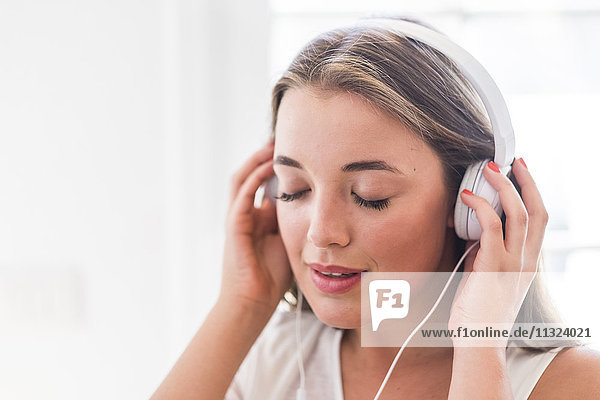 Junge Frau mit geschlossenen Augen Musik hören mit Kopfhörer Junge Frau mit geschlossenen Augen Musik hören mit Kopfhörer