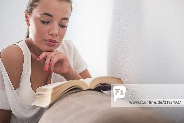 Junge Frau liest Buch auf der Couch