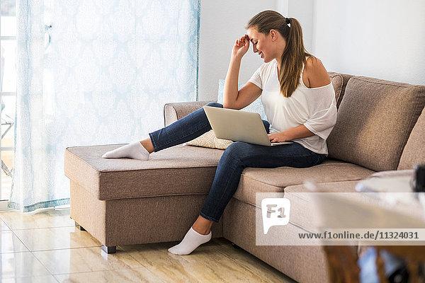 Lächelnde junge Frau sitzt auf der Couch mit Laptop
