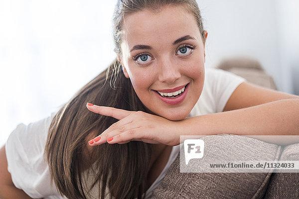 Porträt einer lächelnden jungen Frau auf der Couch