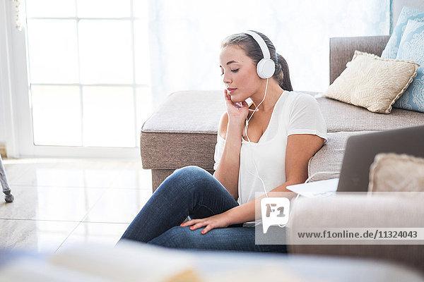 Junge Frau sitzt auf dem Boden des Wohnzimmers und hört Musik mit Kopfhörern.