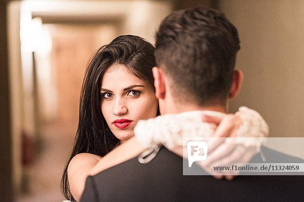 Porträt der Braut  die den Bräutigam umarmt