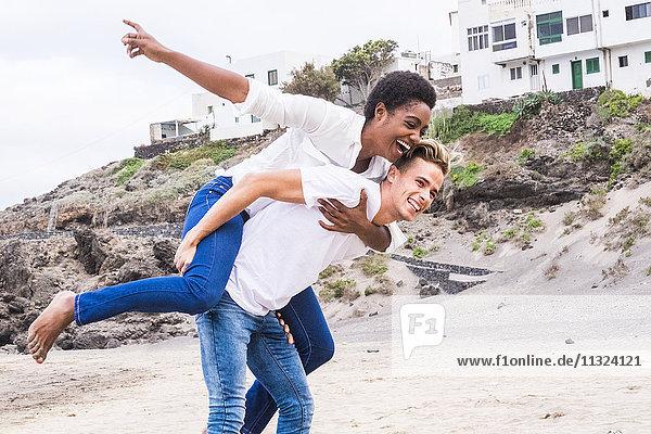 Junges Paar  das vorgibt  am Strand zu fliegen.