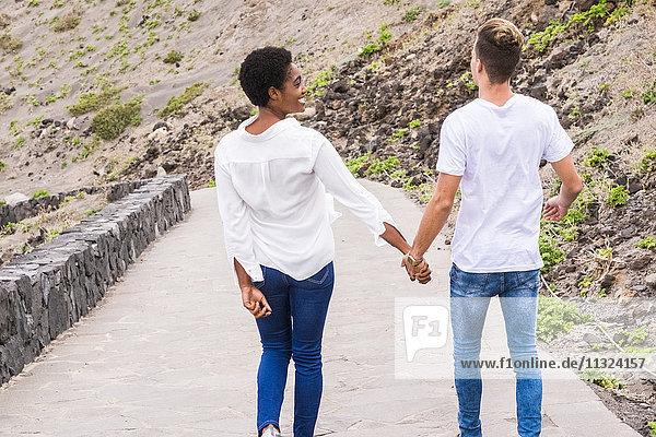 Ein glückliches junges Paar geht an den Strand.