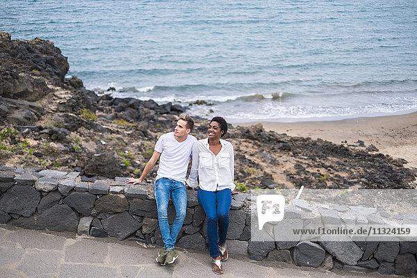 Junges Paar auf Steinmauer an der Küste sitzend