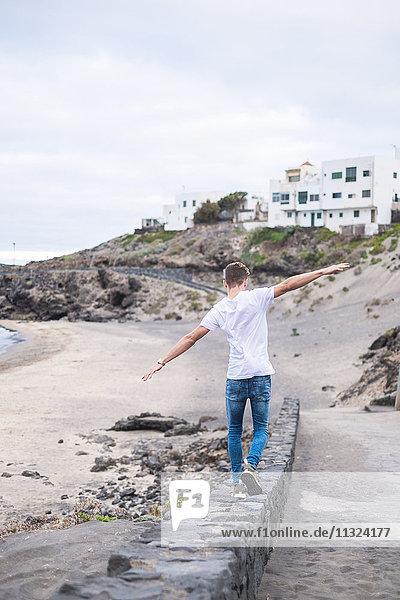 Rückansicht eines jungen Mannes  der an einer Wand am Strand balanciert.