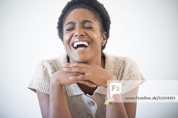 Porträt einer lachenden jungen Frau mit geschlossenen Augen