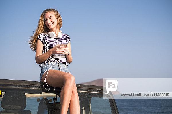 Junge Frau auf dem Auto am Strand sitzend