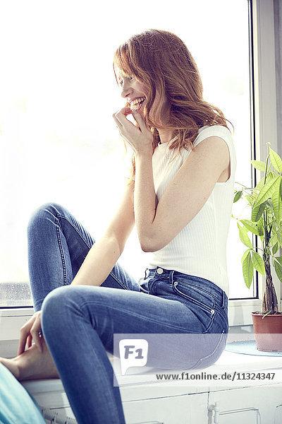 Lachende rothaarige Frau auf Fensterbank sitzend