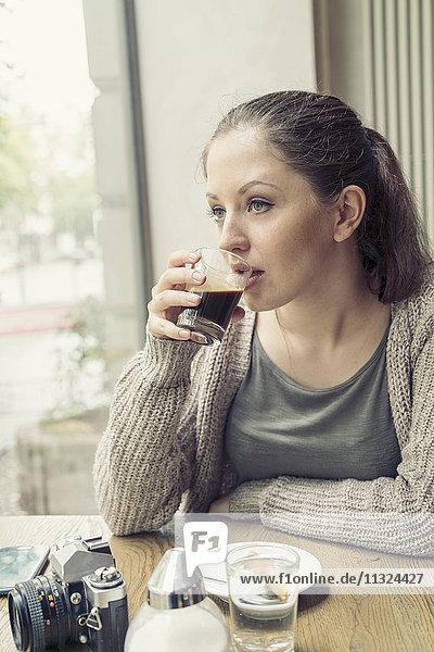 Junge Frau mit Kamera beim Kaffeetrinken im Café