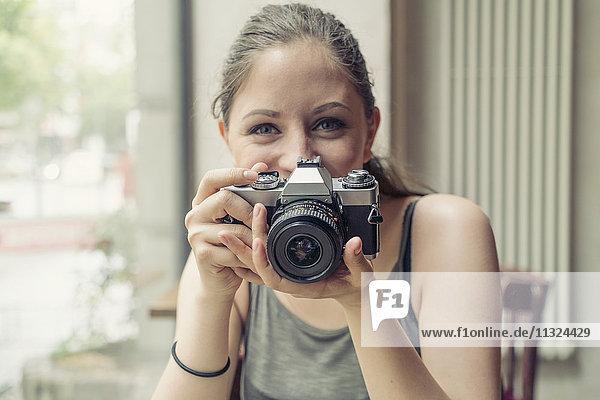 Porträt einer lächelnden jungen Frau  die eine Kamera hält.